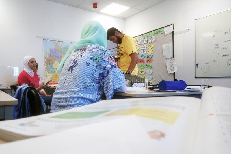 Migranter från Afrika, Asien och Mellanösten lär tyskt i gruppen av den internationella skolan Inlingua i Halle Saale, arkivbilder