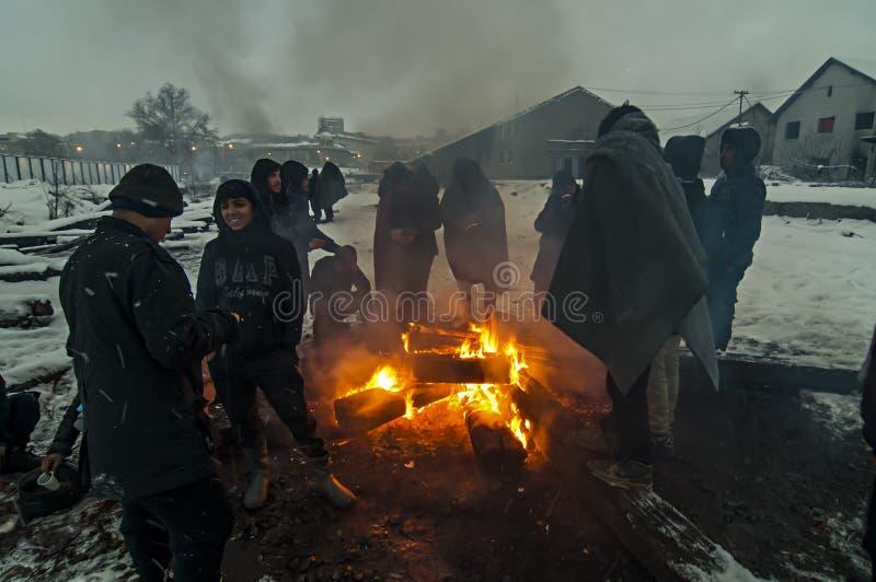 Migranter värmas över en brand i snön och det kalla vädret royaltyfri fotografi
