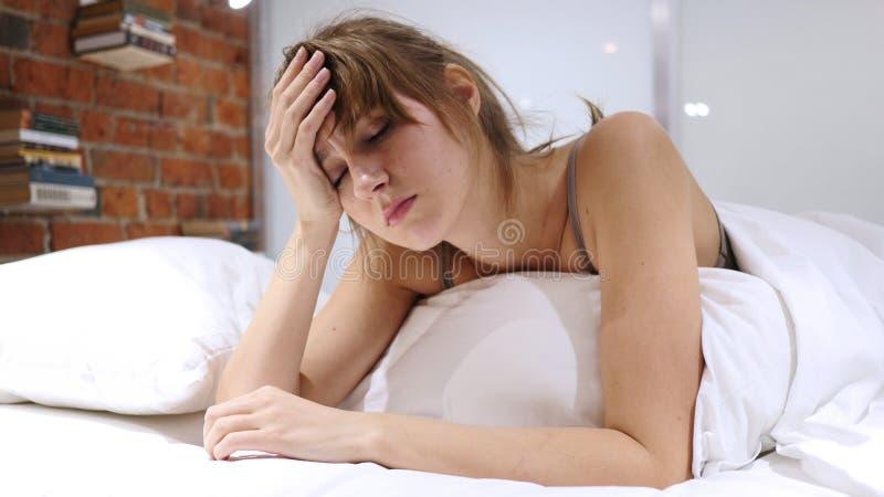 Migrena, frustracja, kobieta z stresu lying on the beach w łóżku obraz stock
