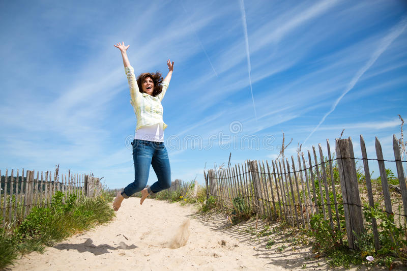 Miidle aged woman jumping on the beach. Happy middle aged woman jumping on the beach crazy for vacation royalty free stock photos