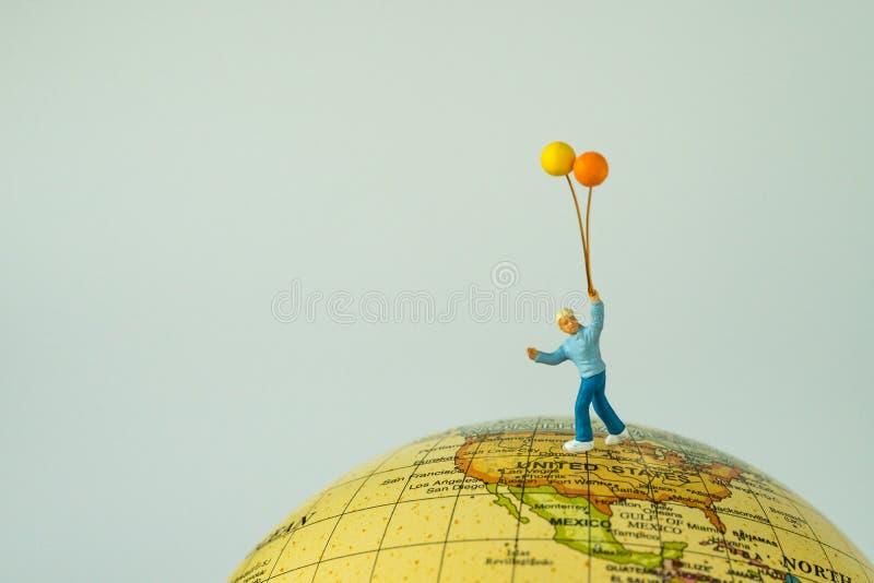 Miiniature人计算拿着气球的愉快的孩子站立  免版税库存图片