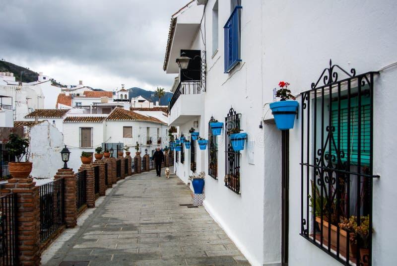 MIJAS SPANIEN - FEBRUARI 08, 2015: En gata av den Mijas pueblobyn som dekoreras med blåa blomkrukor royaltyfria foton