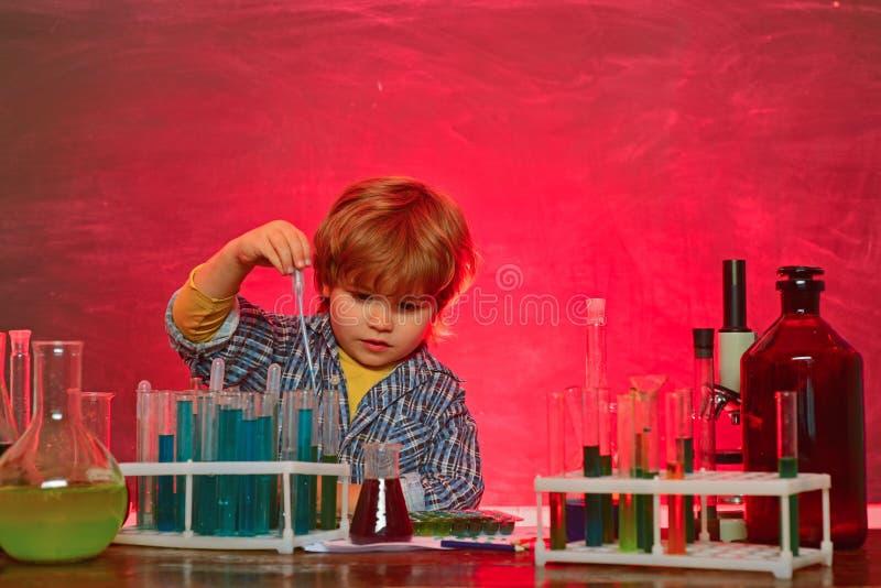 Mijn chemieexperiment Vrolijk glimlachend weinig jongen die pret hebben tegen blauwe muur Thuis het leren Schoolchemie stock afbeeldingen