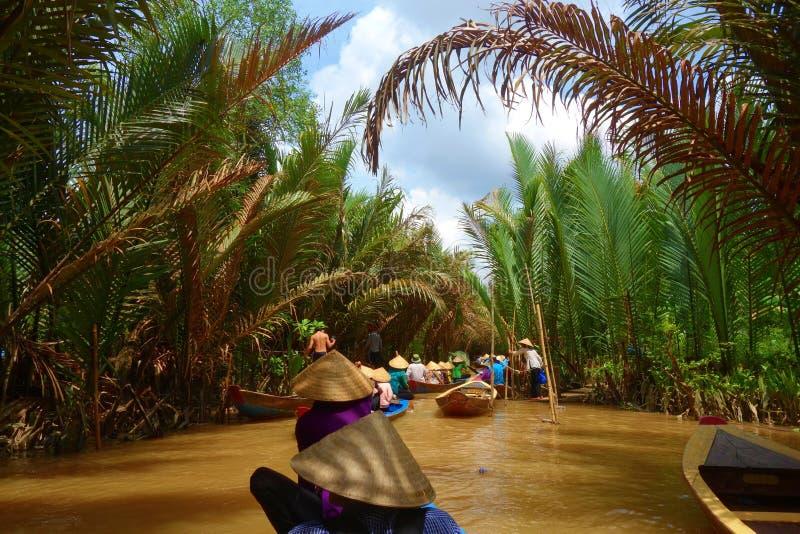 Mijn Tho, Vietnam: Toerist bij Mekong cruise van de Rivier de Deltawildernis met niet geïdentificeerde craftman en vissers het ro royalty-vrije stock fotografie