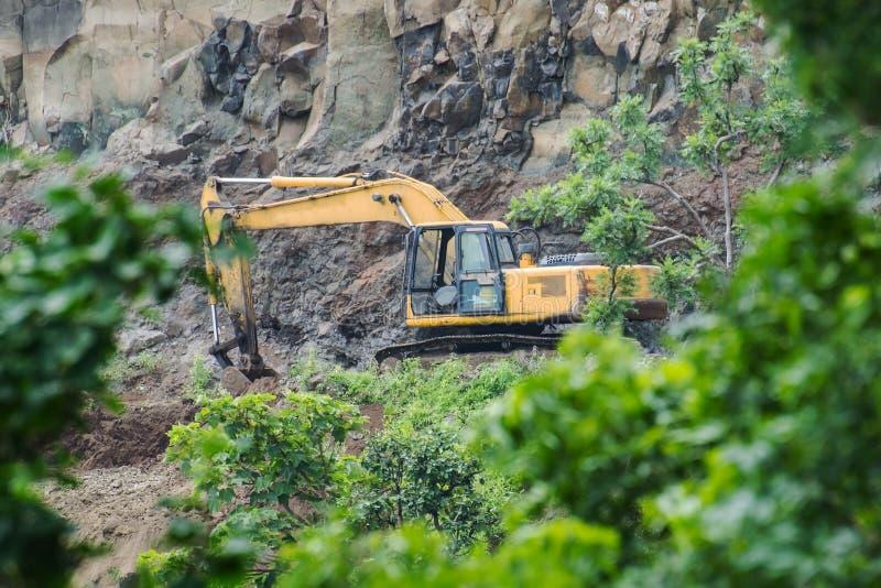 Mijnbouw door Graafwerktuig Backhoe Digger in Bos stock afbeelding
