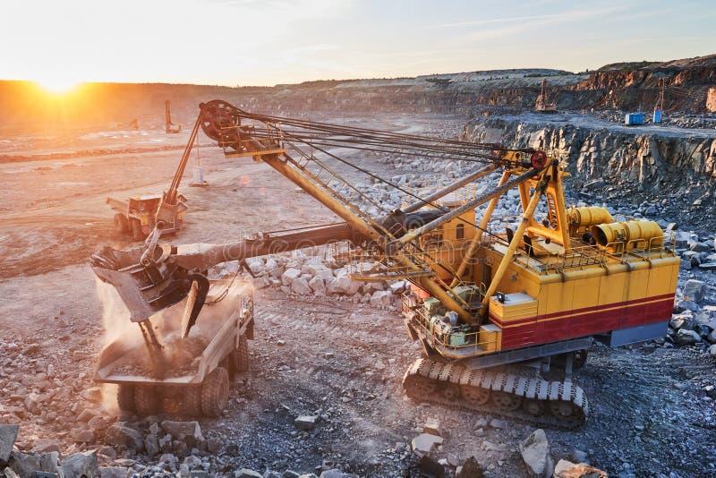 mijnbouw het graniet of het erts van de graafwerktuiglading in stortplaatsvrachtwagen stock foto