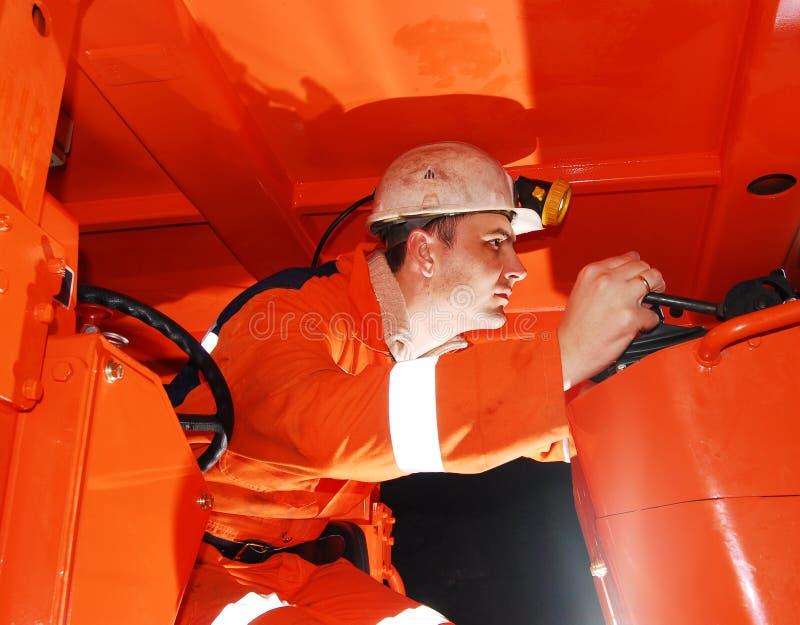 Mijnwerker die zware machines in werking stelt stock foto's