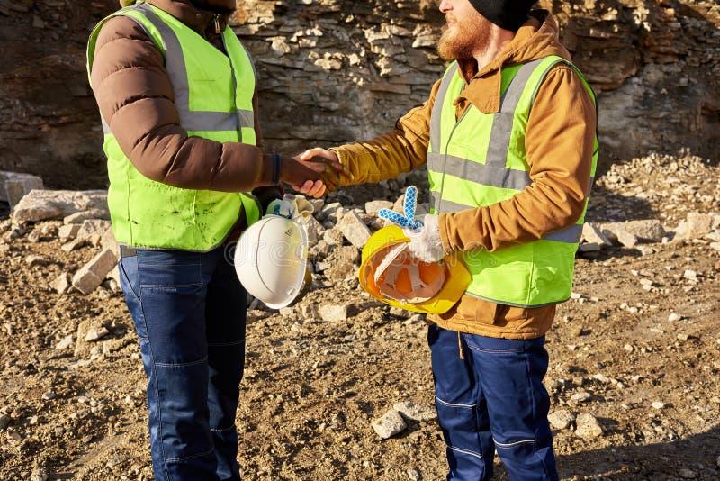 Mijnwerkers die Handen in openlucht schudden stock afbeeldingen