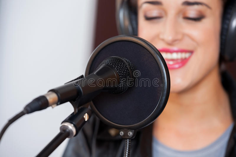 Mike And Condenser With Young Woman Singing In. Closeup of mike and condenser with young woman singing in recording studio stock images