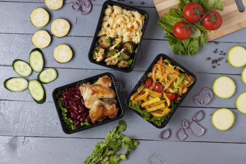 Mikro- Grüns für Mittagspause, Fertiggericht, in den Nahrung-continers auf grauer Tabelle, Zucchinischeiben, unscharfer Hintergru stockbild