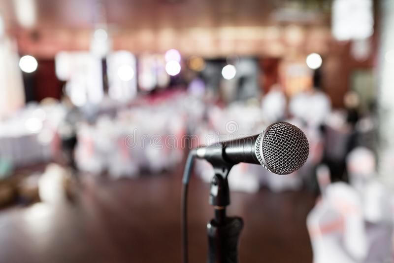 Mikrofon über der Zusammenfassung verwischte Foto des Bankettraumes oder des Seminarraumes mit Leutehintergrund, -Partei oder -si stockfotografie