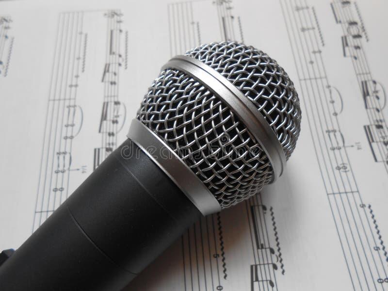Mikrofon auf den Musikanmerkungen stockfotografie
