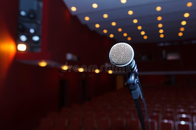 Mikrofon auf einem Hintergrund der dunklen Halle mit Sitzplätzen für Zuschauer stockfoto