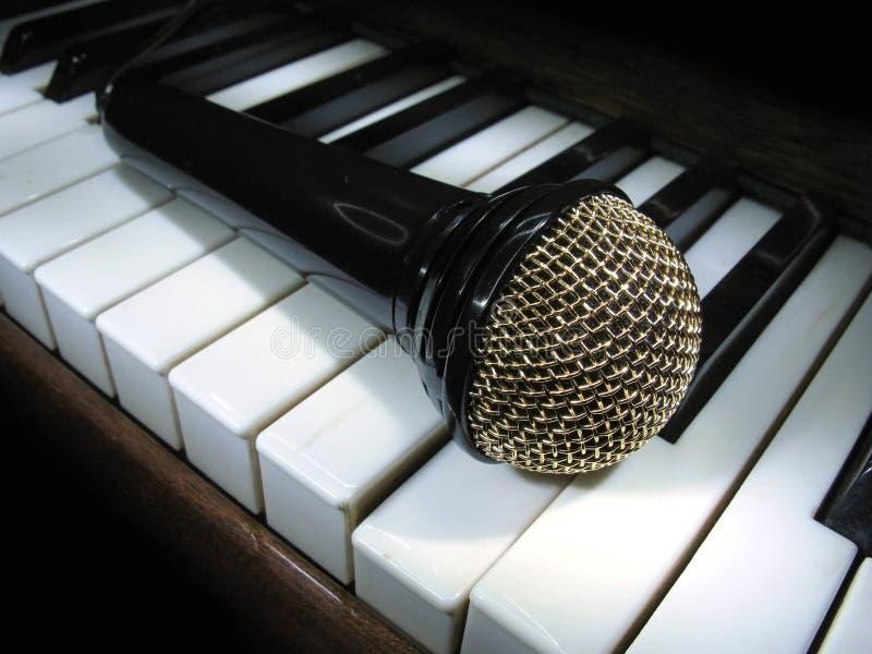 Mikrofon auf Klaviertasten stockbild