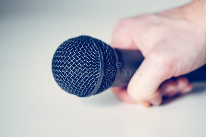 Mikrofon, das in der Hand mit weißem Hintergrund hält lizenzfreie stockfotos