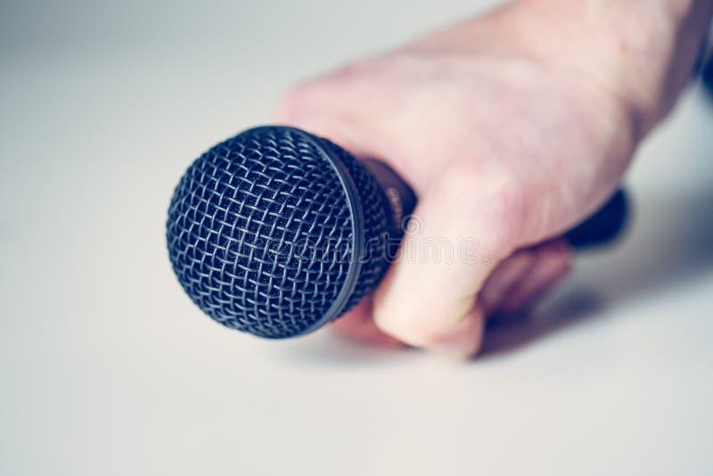 Mikrofon, das in der Hand mit weißem Hintergrund hält lizenzfreie stockfotografie