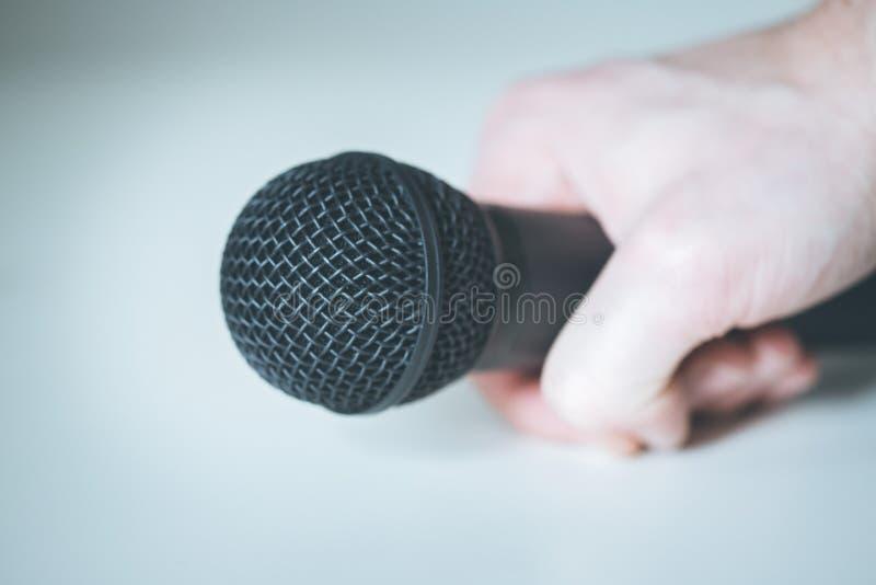 Mikrofon, das in der Hand mit weißem Hintergrund hält stockbilder