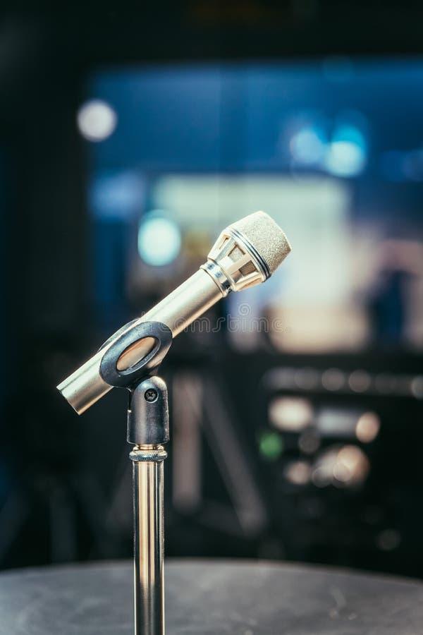 Mikrofon i den anteckna studion, utrustningen och belysningen i den oskarpa bakgrunden royaltyfri bild