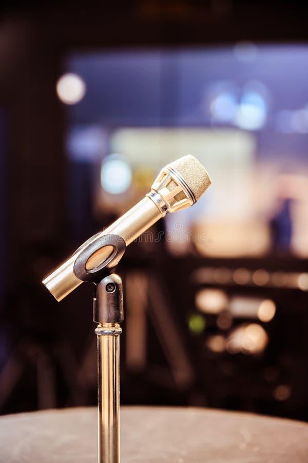 Mikrofon i den anteckna studion, utrustningen och belysningen i den oskarpa bakgrunden fotografering för bildbyråer