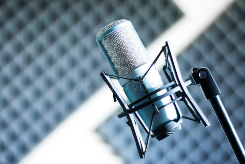 Mikrofon i en yrkesmässig inspelning- eller radiostudio, solid isolering i den oskarpa bakgrunden royaltyfri fotografi