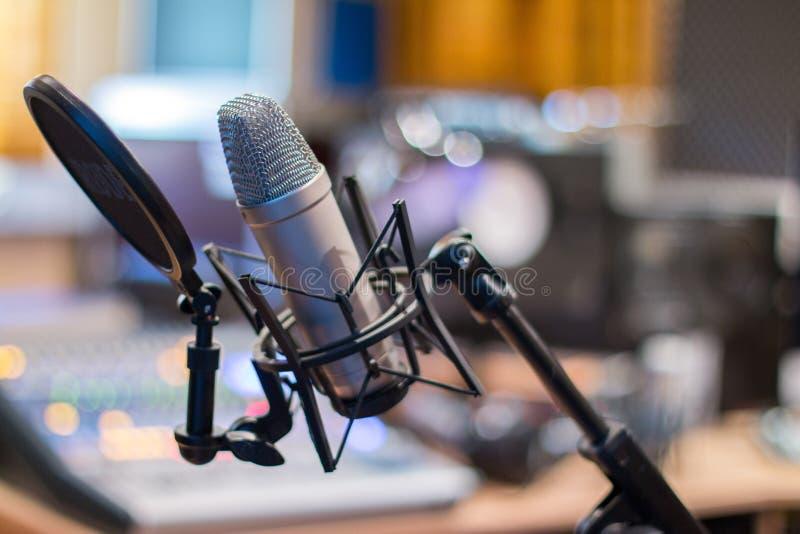 Mikrofon i en yrkesmässig inspelning- eller radiostudio, utrustning i den oskarpa bakgrunden royaltyfri foto