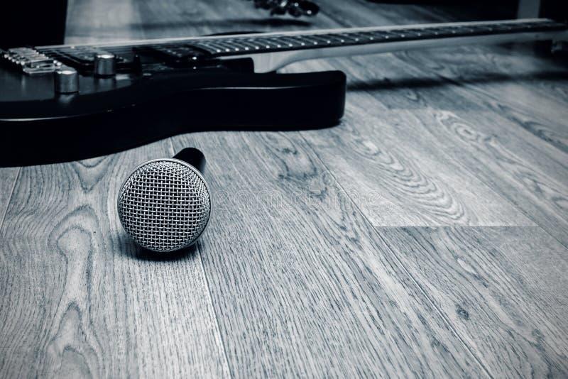 Mikrofon i gitara na drewnianym tle w czerni i bieli zdjęcia royalty free