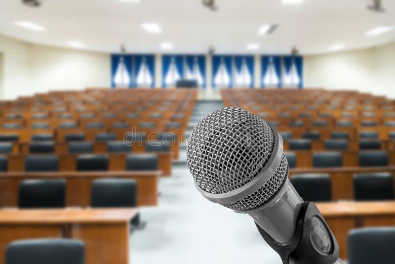 Mikrofon mit unscharfem Foto des leeren Konferenzsaales oder der Samen stockbild