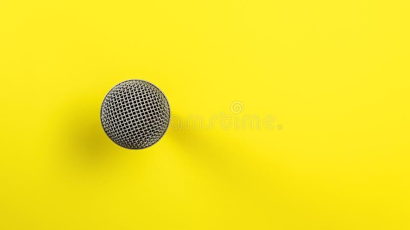 Mikrofon na żółtej płycie, bezpośredni widok w dół, tylko piłka z widoczną siatką, która wygląda abstrakcyjnie fotografia stock
