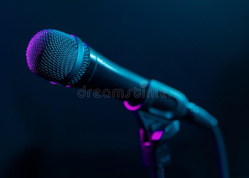 Mikrofon na czarnym tle z kolorowymi menchiami i turkus zaświecamy Muzyka, koncertowy pojęcie fotografia stock