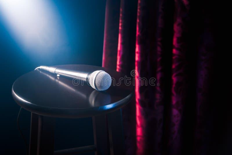 Mikrofon na drewnianej stolec na stojaku w górę komediowej sceny z odbłyśnika promieniem, wysokiego kontrasta wizerunek zdjęcia royalty free