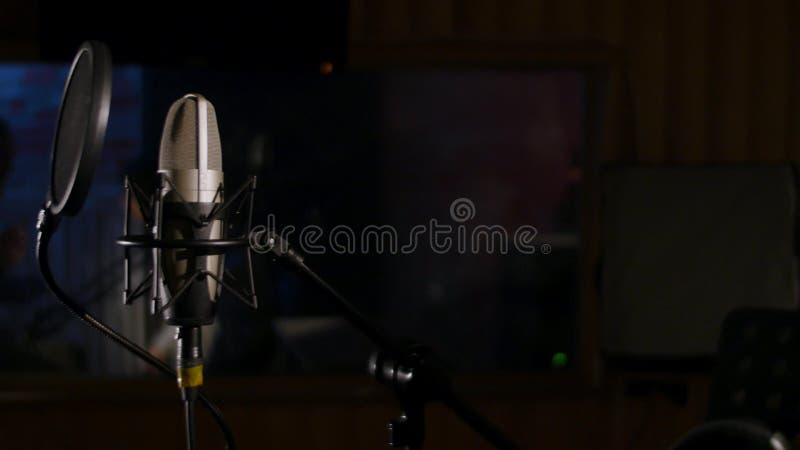 Mikrofon na stojaku lokalizować w muzyki pracowniany magnetofonowy budka pod depresja klucza światłem zdjęcia stock