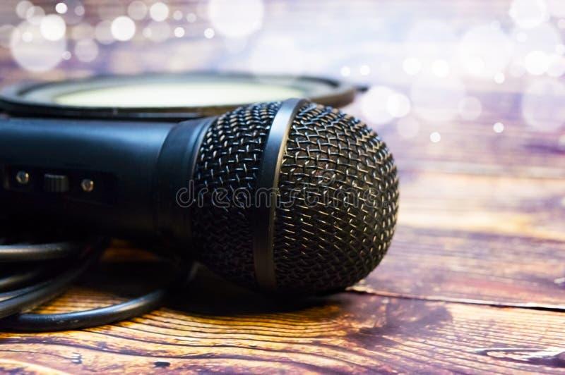 Mikrofon och högtalare på bakgrunden av oskarpa partiklar och trätabellen royaltyfria bilder