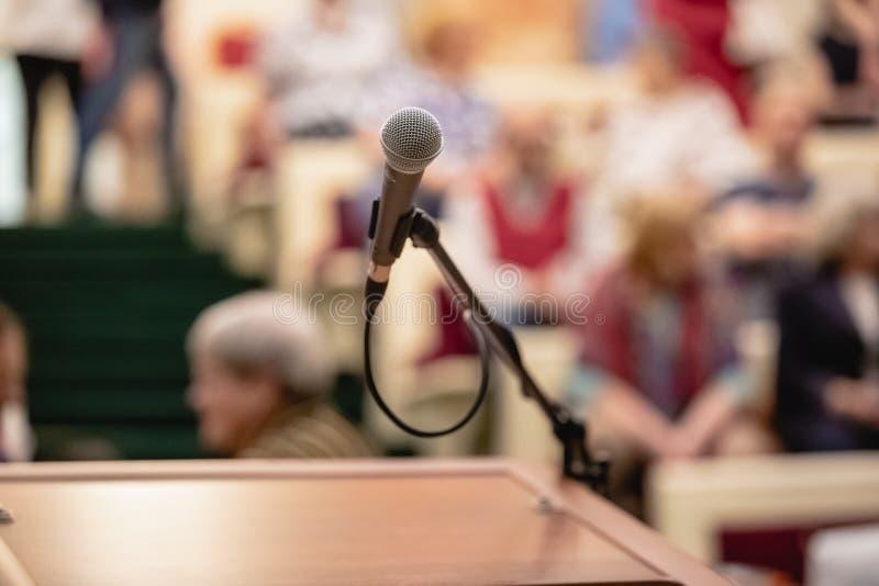 Mikrofon på abstrakt suddigt av anförande i seminariumrum eller talande ljus för konferenskorridor, händelsebakgrund royaltyfria foton