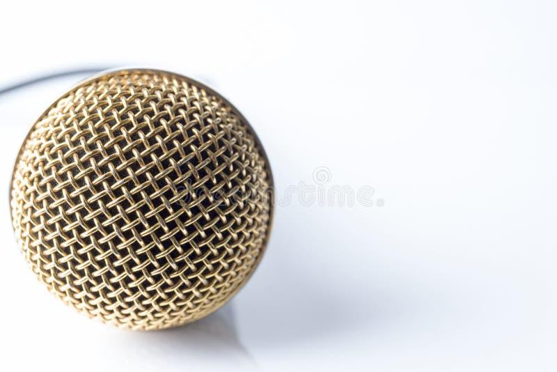 Mikrofon på en vit bakgrund med en guldpläterad dysa royaltyfria foton