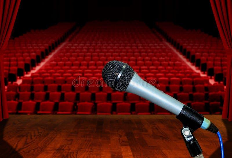 Mikrofon på etapp med tomma salongplatser royaltyfri foto