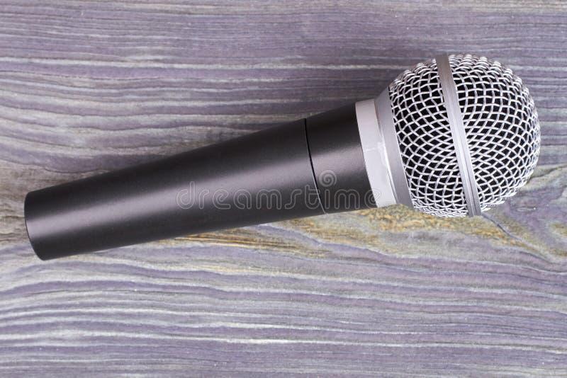 Mikrofon på grå träbakgrund arkivbilder
