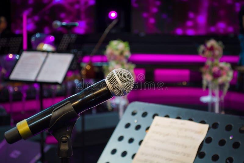 Mikrofon przeciw i muzyczne notatki zamazujemy kolorowego lekkiego backgroun zdjęcia stock