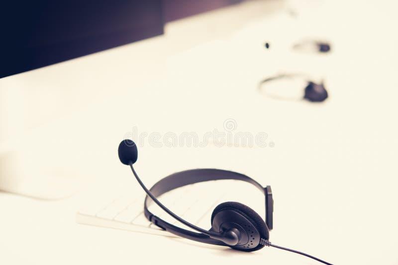 Mikrofon słuchawki na stole z komputerowymi słowami kluczowymi zdjęcie royalty free