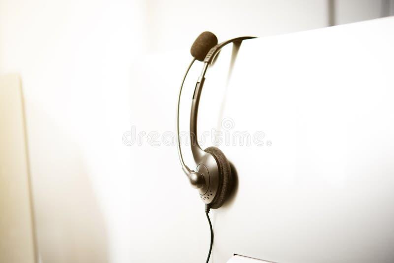 Mikrofon słuchawki obwieszenie na komputerowym monitorze zdjęcie stock