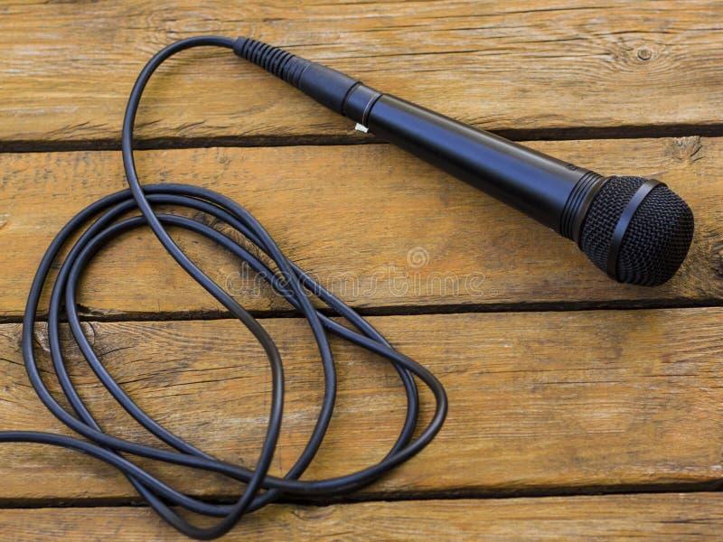 Mikrofon som ligger på en trätabell royaltyfria foton