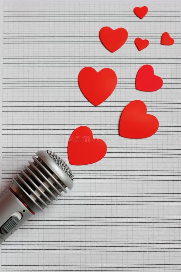 Mikrofonen och pappers- röda hjärtor lokaliseras på en ren musikanteckningsbok Begreppet av musik och förälskelse valentin för da royaltyfri foto