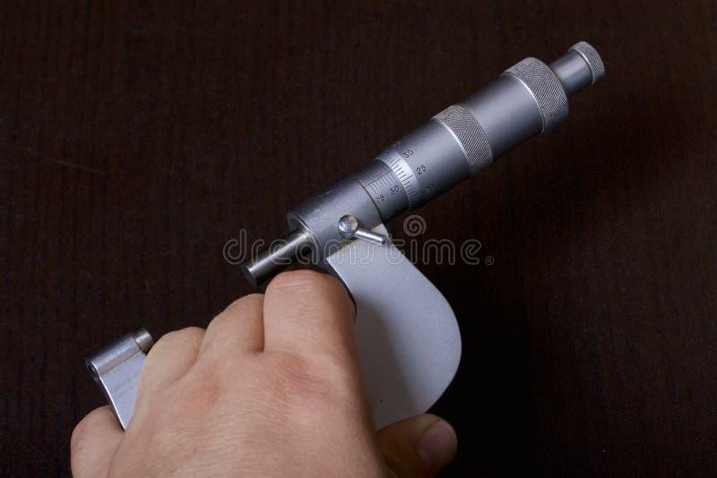 Mikrometer med en rund skala för yttre mätningar och ett mäta område av mm 25 - 50 I handen för man` s På en mörk backg royaltyfri foto