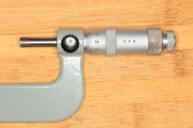 Mikrometer som ligger på ett träbräde royaltyfria foton