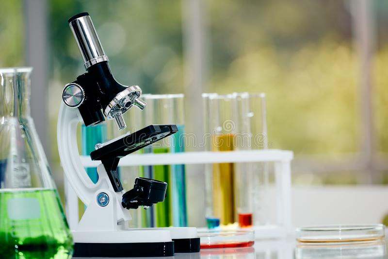 Mikroskop på tabellen med laboratoriumutrustning i kemisk labb royaltyfri fotografi