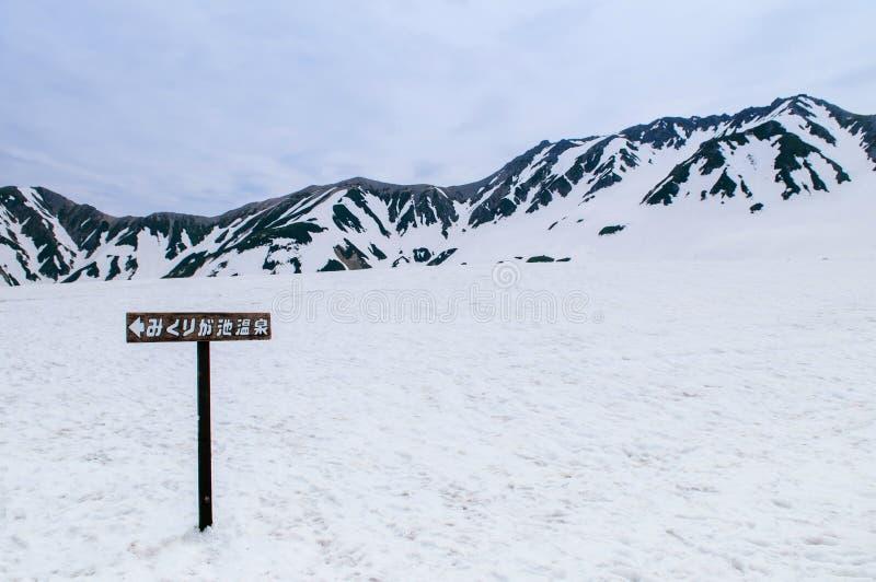 Mikurigaike onsen trätecknet på snölandskap av Tateyama Kuro arkivfoton