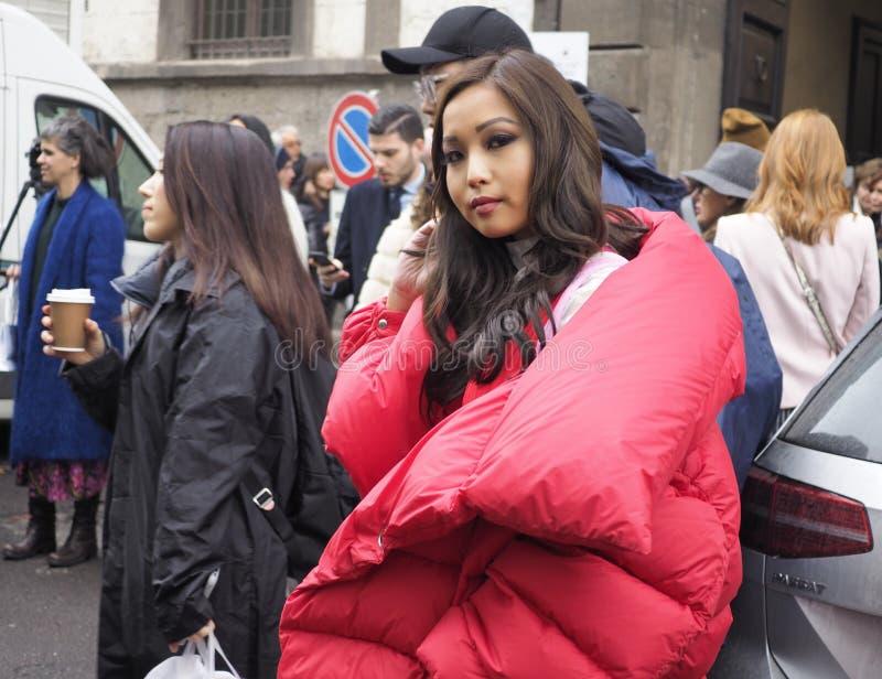 MILÁN - 22 DE FEBRERO DE 2018: Mujer asiática de moda que presenta para los fotógrafos antes de desfile de moda de GENNY, Milan F fotografía de archivo