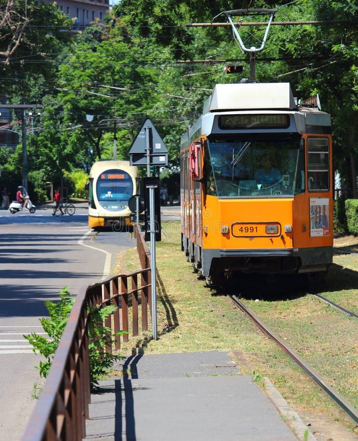Milán, Italia - 18 de junio de 2017: El tranvía de transporte público ferroviario de Milán llega a su parada con otro vehícul imagenes de archivo