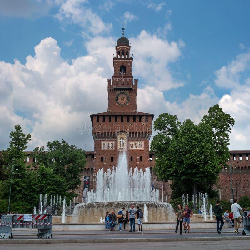 Milán, Italia - 9 de mayo de 2018: Entrada principal al castillo de Sforza - Castello Sforzesco y fuente Turistas en fotos de archivo libres de regalías
