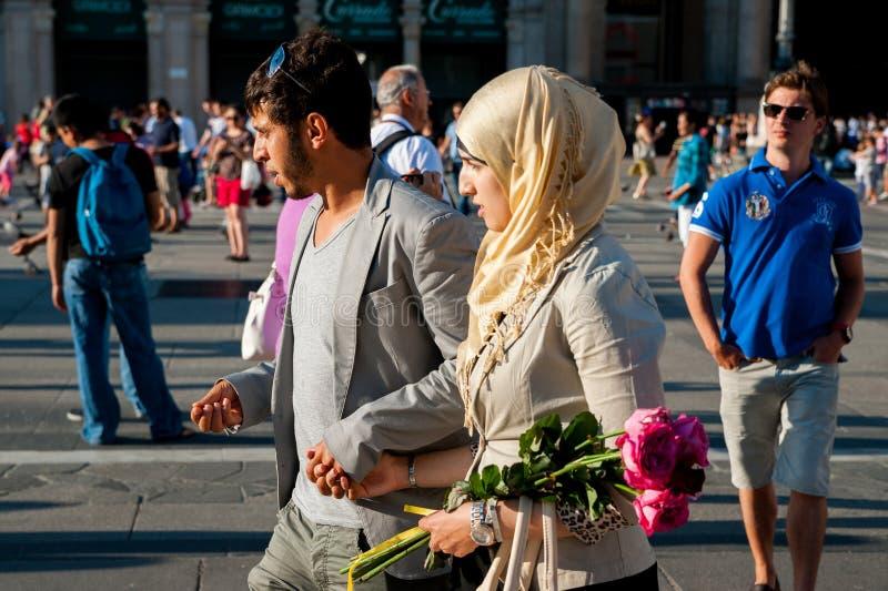 Milão, Itália - 20 de junho de 2018: os pares de povos marroquinos muçulmanos novos apenas casaram a caminhada no centro da cidad fotos de stock