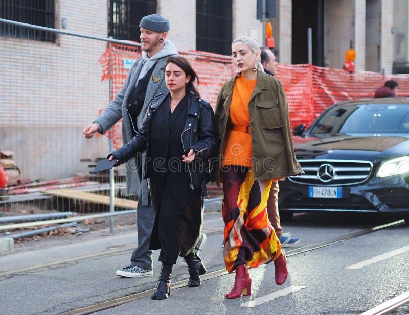 MILÃO - 13 de janeiro: Duas mulheres elegantes que andam na rua após o desfile de moda de NEIL BARRET, durante Milan Fashion Week imagens de stock royalty free